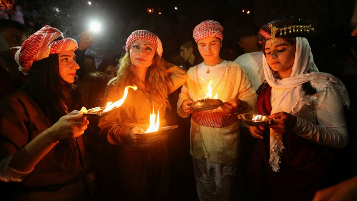 Yezidis light candles and paraffin torches during a ceremony to celebrate the New Year in Dohuk province, Iraq, in 2017.