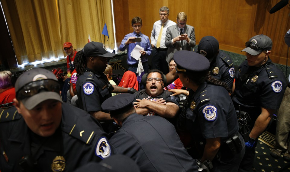 A police officer removes a disabled protester form a Congressional hearing.
