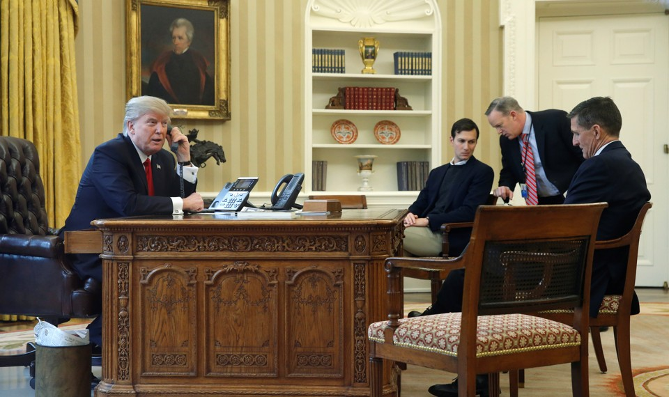 President Trump, accompanied by senior aides, makes a phone call in the Oval Office.
