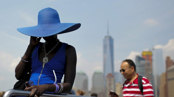 A woman in a sunhat speaks on a cellphone in front a city skyline.
