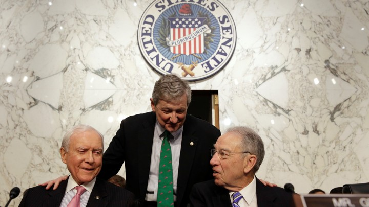 Senator John Kennedy (standing) speaks with Senators Orrin Hatch (left) and Chuck Grassley.