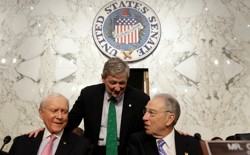 Senator John Kennedy (standing) speaks with Senators Orrin Hatch (left) and Chuck Grassley.