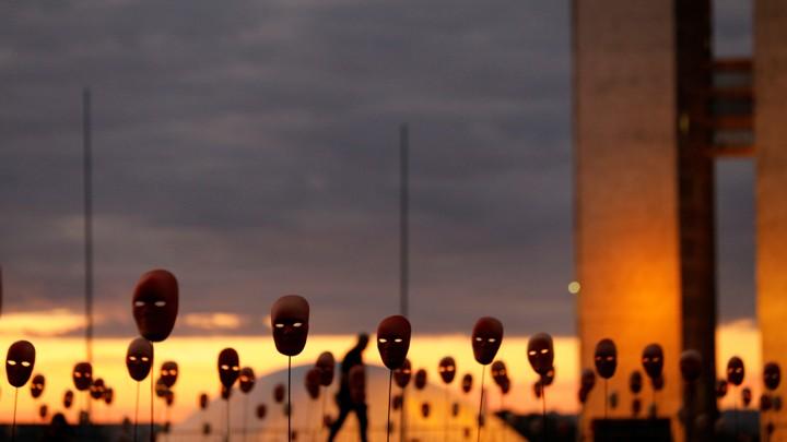 A man walks past masks in Brasilia.
