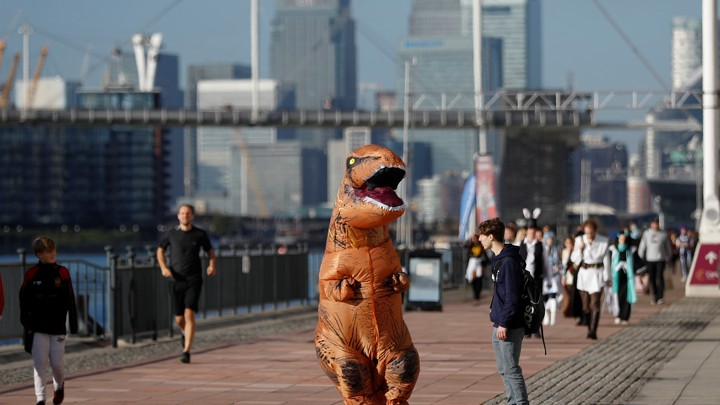 A person in a T-rex costume on a riverside walking path in London