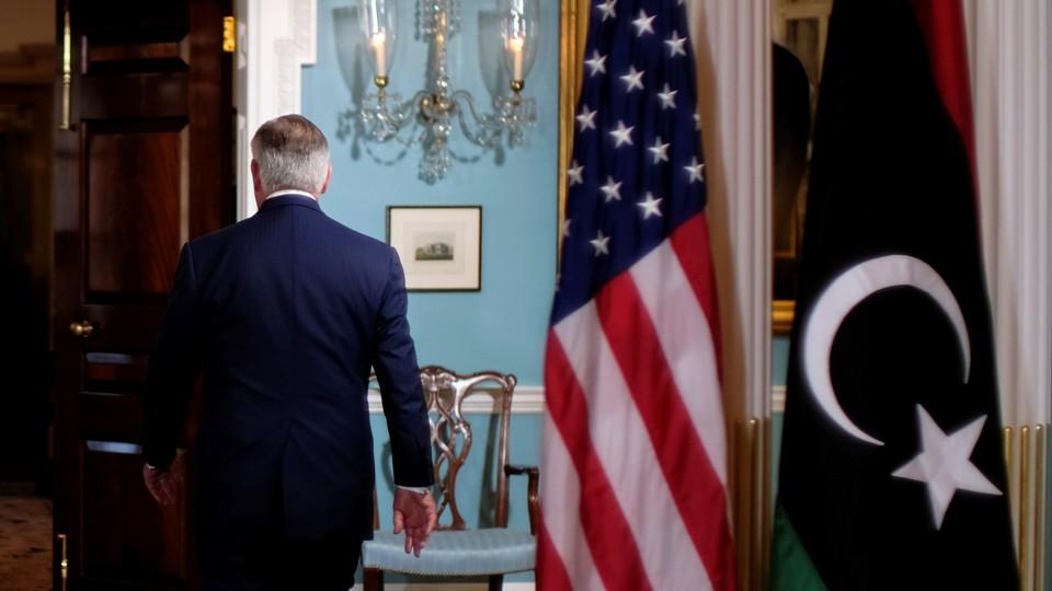 Rex Tillerson walks out of a room.
