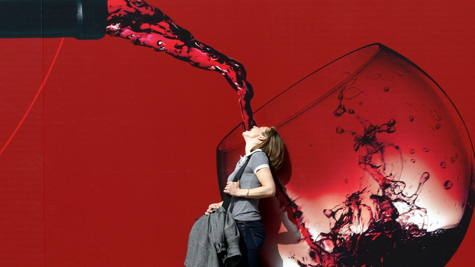 A woman stands with her mouth open in front of a large illustration of red wine being poured into a glass.