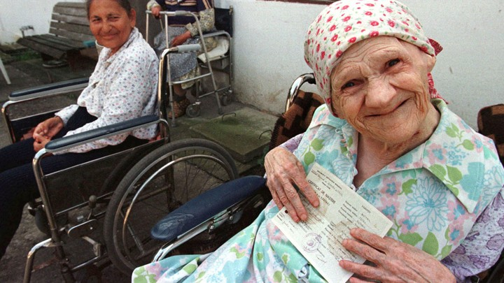 An elderly woman holds her birth certificate at a retirement home.