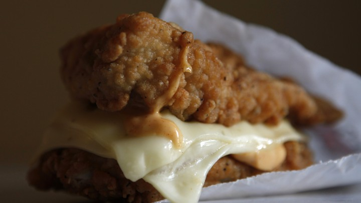 A close-up photograph of a fast-food sandwich made of two chicken tenders with cheese between them.