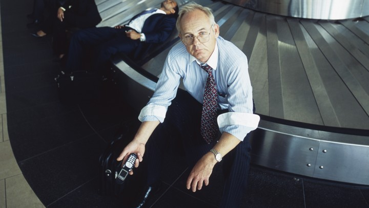 A man in a shirt and tie holds a cellphone and looks upset while sitting on a baggage carousel at an airport.
