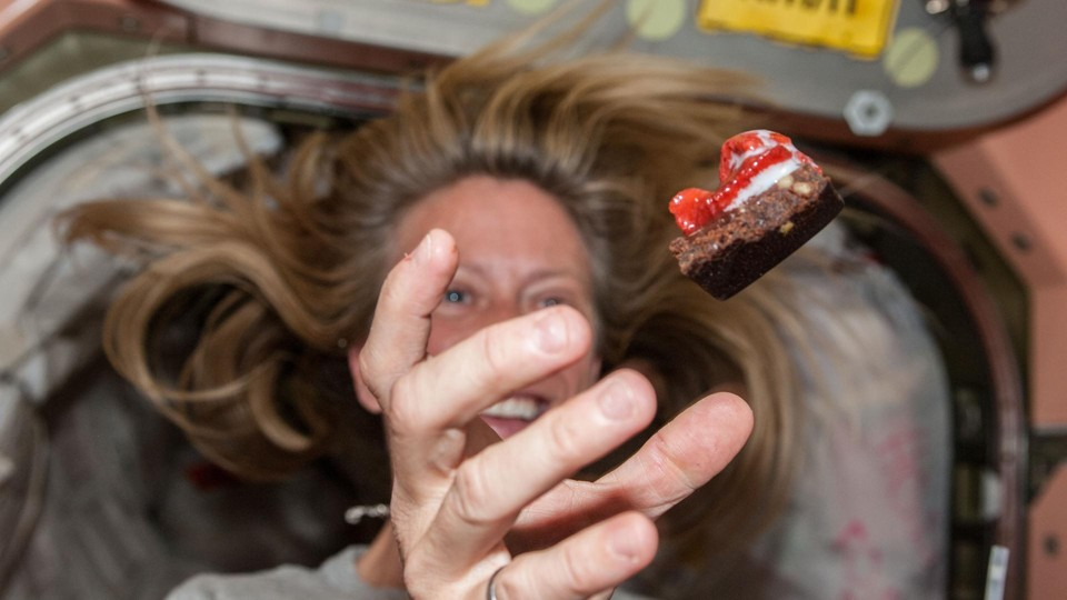 NASA astronaut Karen Nyberg floats a piece of food during mealtime.