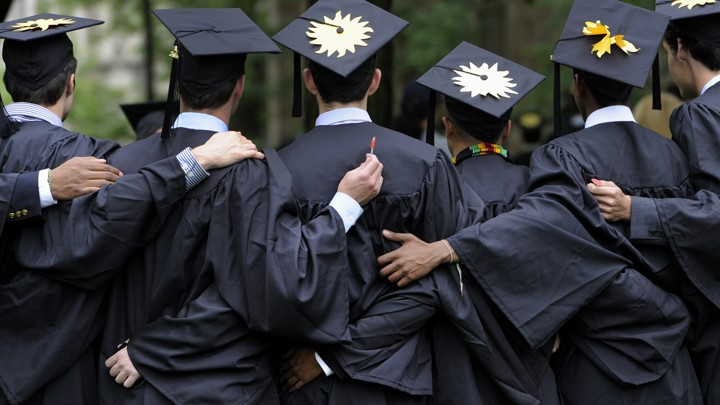 College graduates are shown from behind, with arms around each other