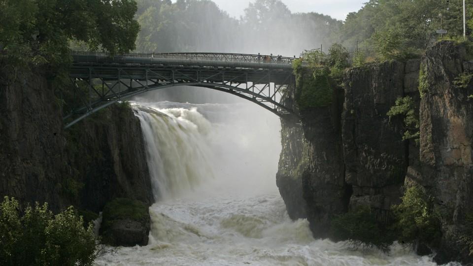 A swollen river under a bridge