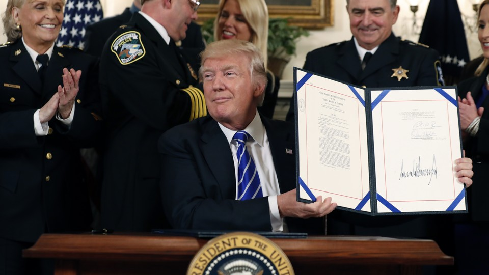 President Trump holds a signed bill in at the White House.