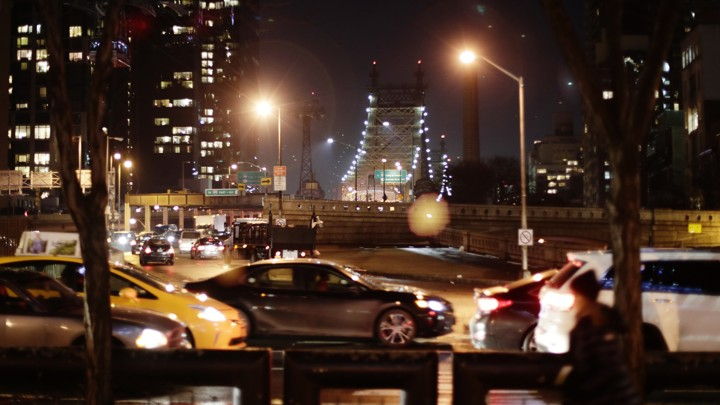 Cars driving at night in front of the Queensboro Bridge