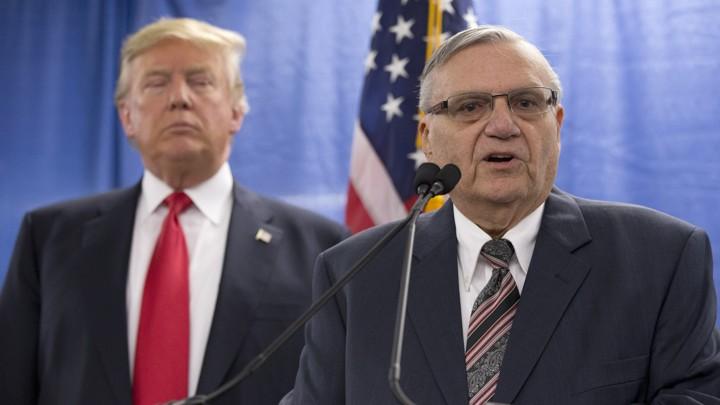 Joe Arpaio speaks with President Trump behind him.