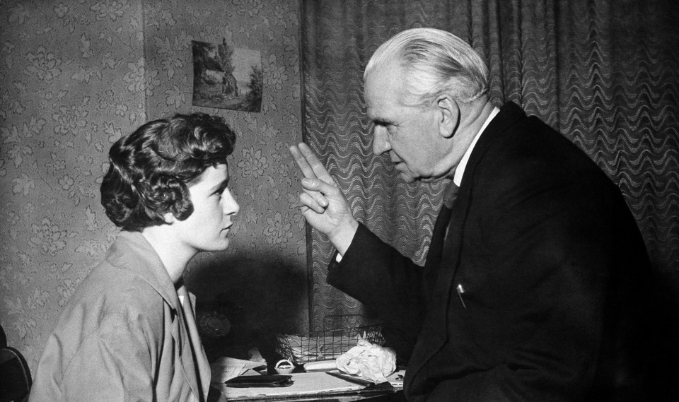 In a black-and-white photo, an old man holds his fingers in front of a young girl's face.