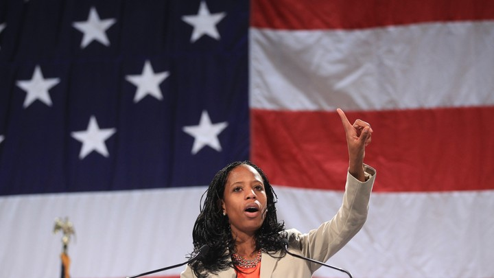Mia Love stands in front of an American flag.