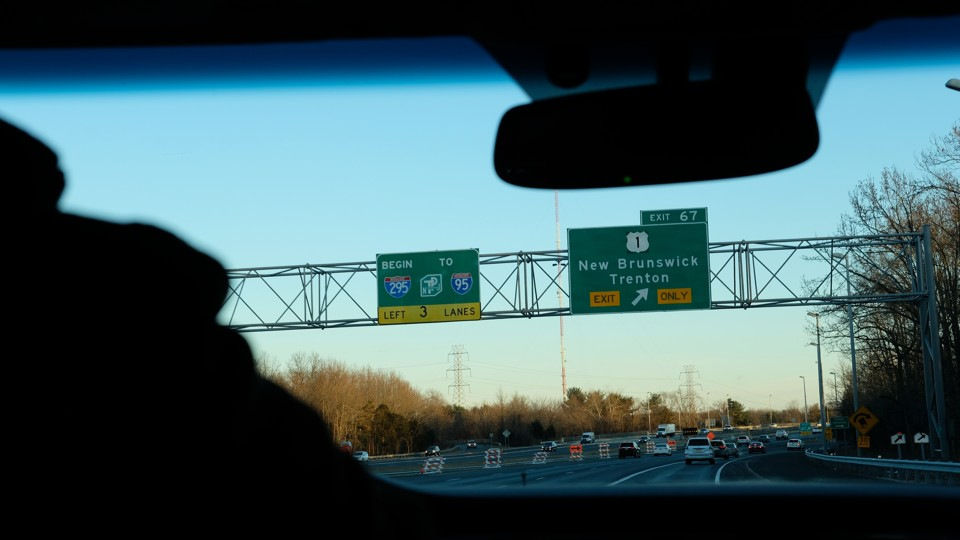 Highway signs for I-95 and I-295 at the exit for New Brunswick in New Jersey, viewed through a car windshield