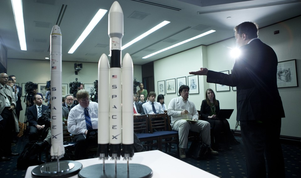 """A person gestures to two models of rockets labeled """"SpaceX."""""""