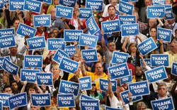 A crowd of people holding blue signs that say THANK YOU