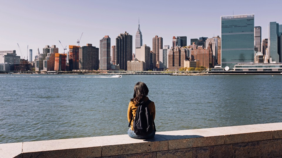 A young woman gazes at Manhattan's skyline