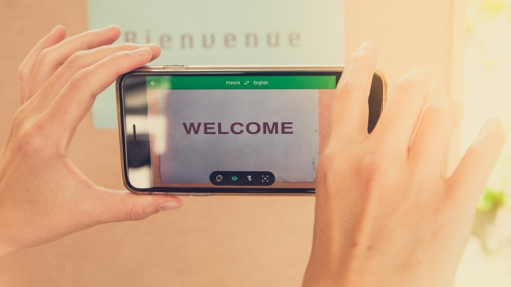 """Hands hold a smartphone in front of a sign saying """"Bienvenue,"""" and the smartphone reads """"Welcome."""""""