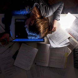 A woman sleeping on top of a laptop, surrounded by papers