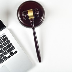 A gavel rests next to a laptop keyboard.
