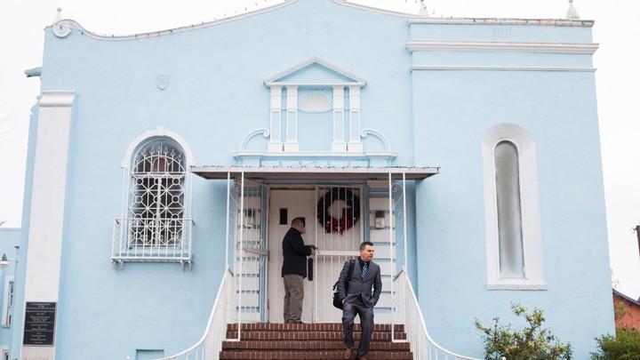 A pastor exits a blue church.