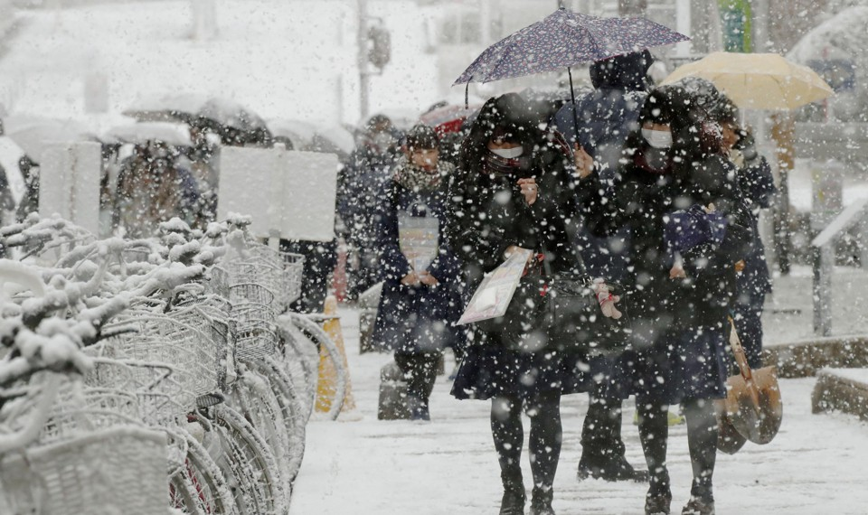 Students walk with umbrellas in the snow.