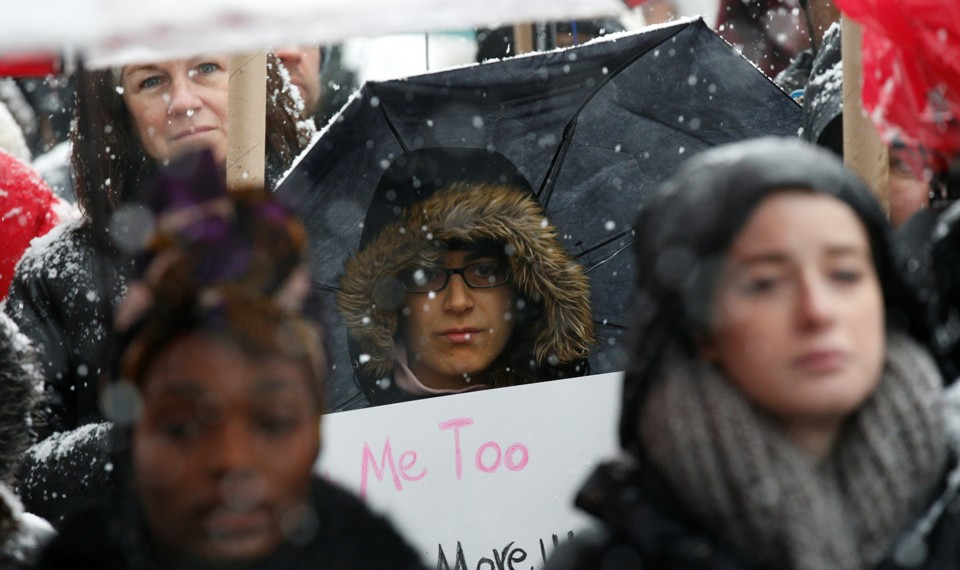 """A woman holds a """"Me Too"""" sign."""