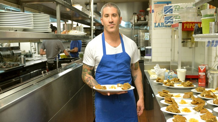 Michael Solomonov holds a plate of food next to a row of plates of food on a restaurant kitchen counter.