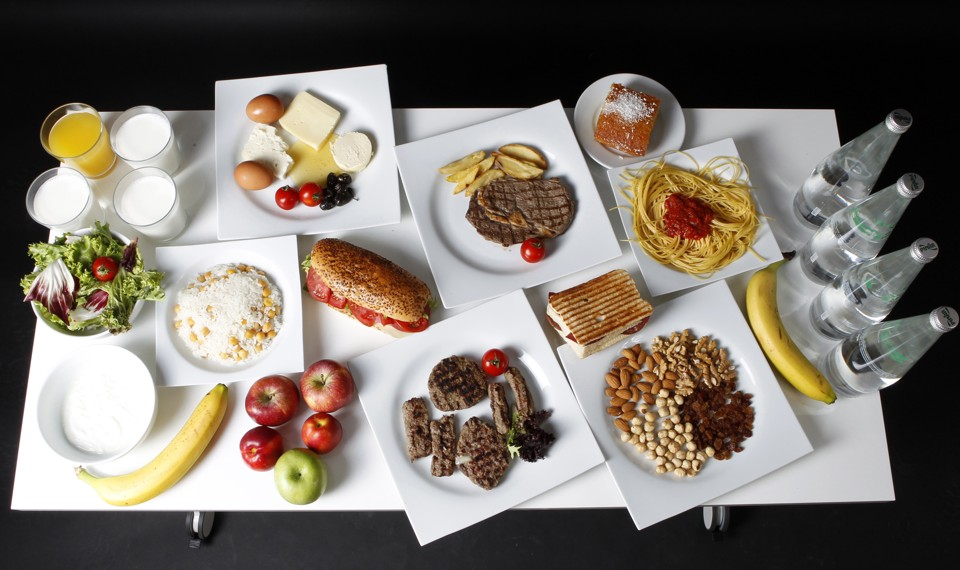 A table containing salad, fruit, water, pasta, meats, sandwiches, cheese, eggs, juice, and milk