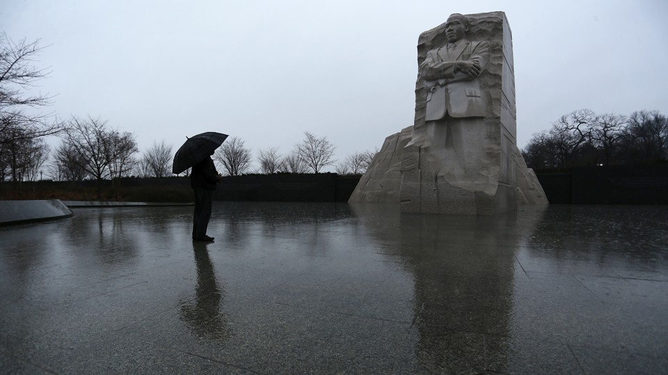 A person, carrying an umbrella, at the Martin Luther King Jr. Memorial in Washington, D.C.