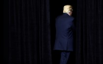 Donald Trump exits a dark stage.