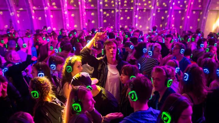 People dance while wearing glowing headphones