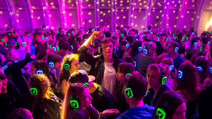 People dance while wearing glowing headphones
