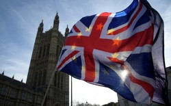 Anti-Brexit demonstrators wave EU and Union flags outside the Houses of Parliament in London onJanuary 30, 2018.