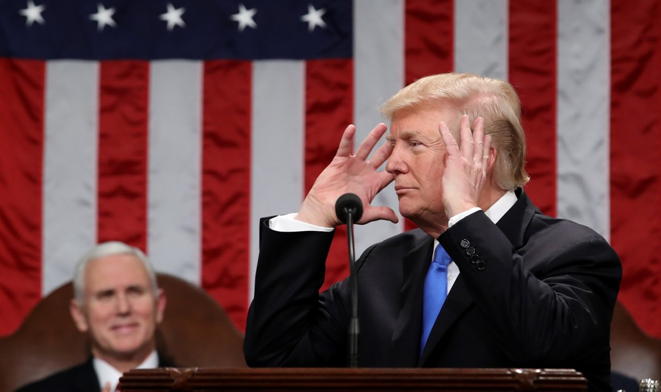 President Donald Trump raises his hands to his head while delivering his first State of the Union address.