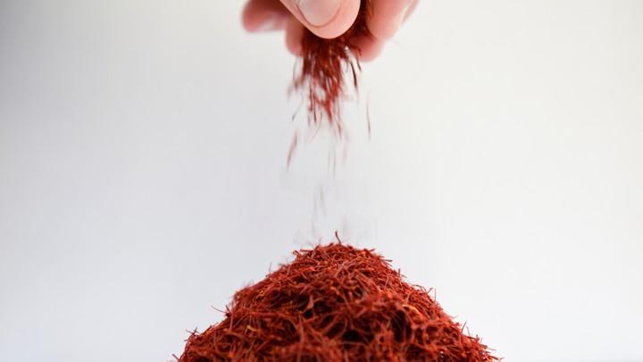 A hand sprinkles saffron into a pile.