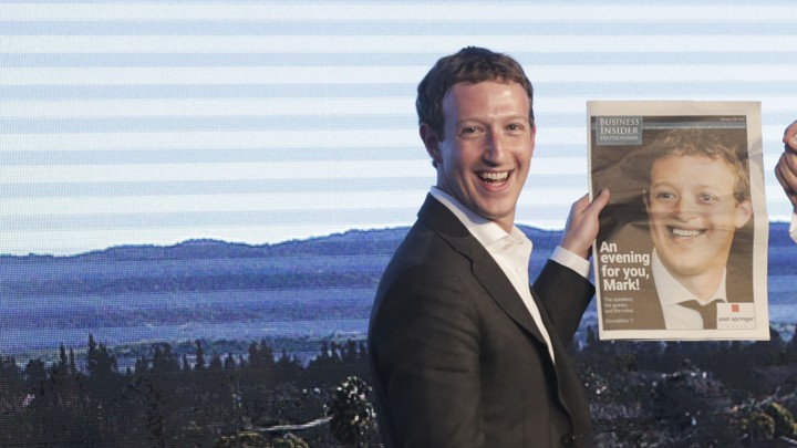 Facebook's Mark Zuckerberg holds a newspaper with a picture of him on it.