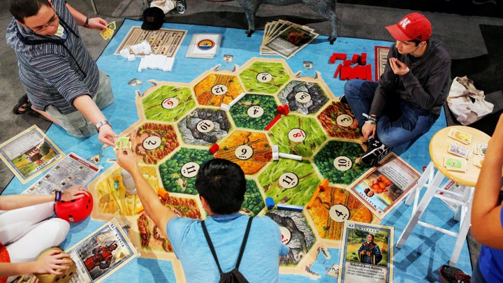 Three young men play the German board game Settlers of Catan