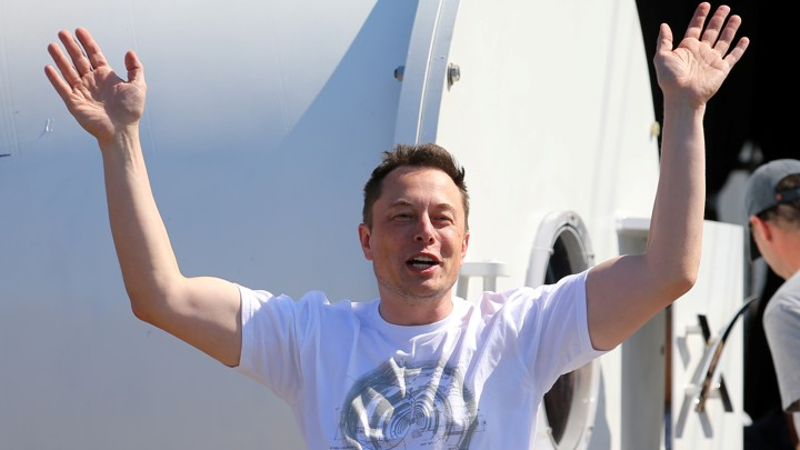 SpaceX's Elon Musk smiles and holds his hands in the air in 2017