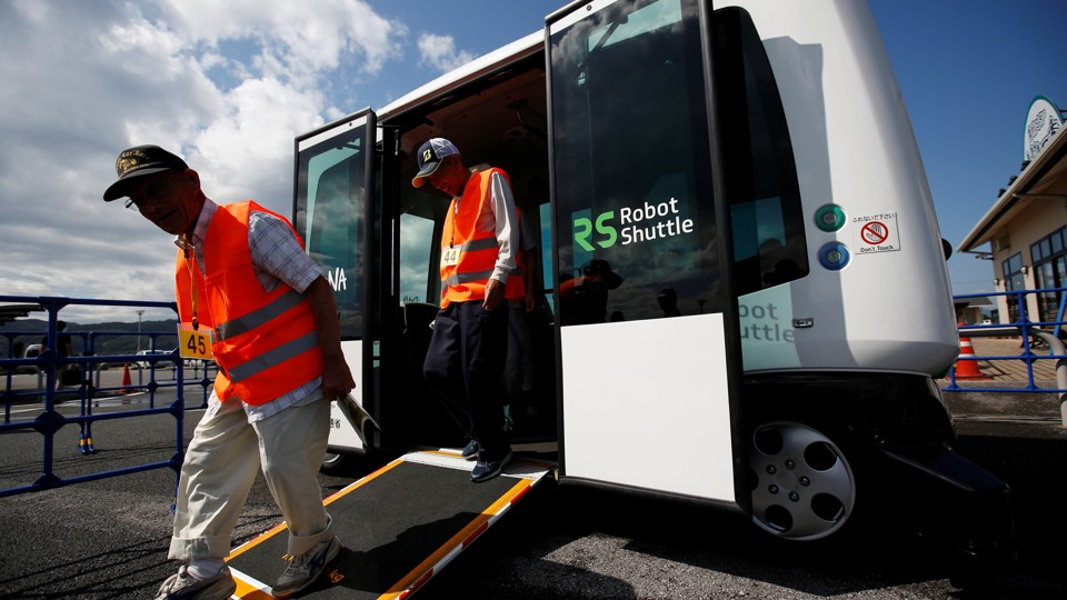 """People in orange vests use a ramp to exit a driverless bus labeled """"Robot Shuttle."""""""