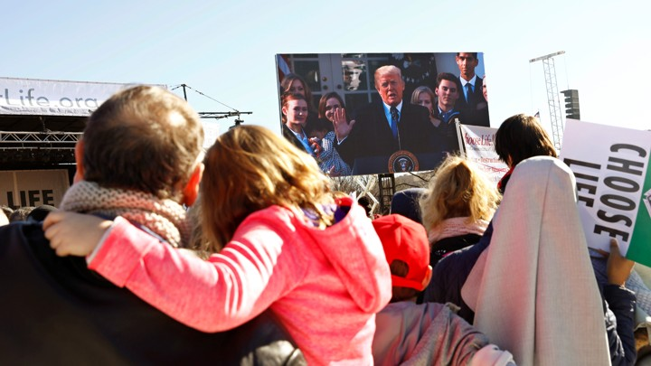 Participants watch as President Trump speaks by satellite from the White House to attendees of the March for Life rally in Washington.