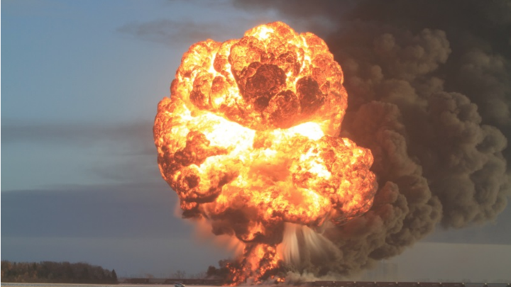A large fireball and smoke rise from a train on a prairie.