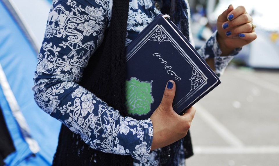 A Muslim refugee holds a Koran in Lesbos, Greece