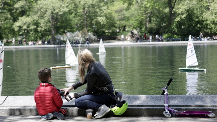 A mother and child look at miniature sailboats.