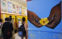 Students walk in a school hallway, next to a mural with two hands holding a flower.