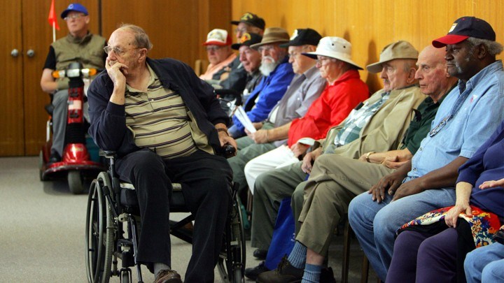 Older people wait in chairs and wheelchairs.